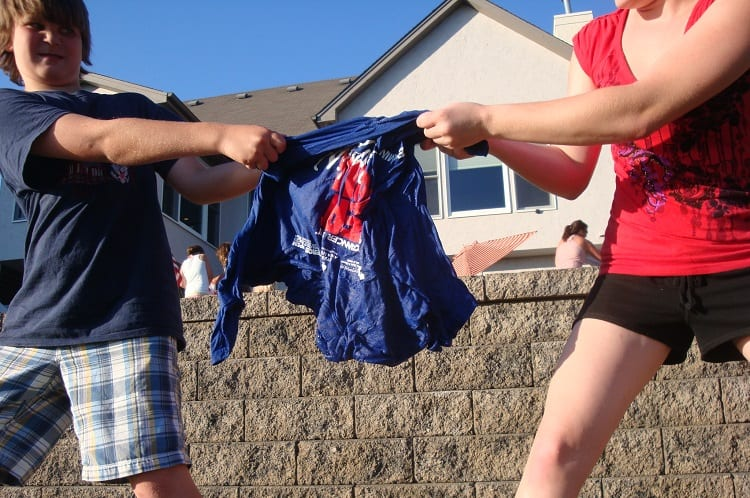 kids trying to unfold a tshirt